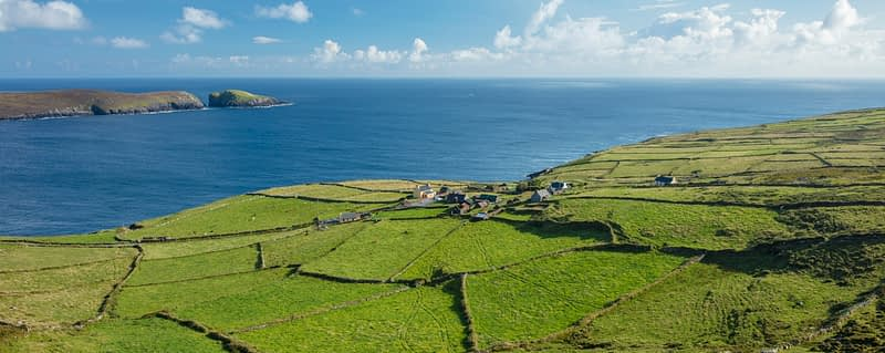 Green fields surround the hamlet of Ballynacallagh, Dursey Island, Beara Peninsula, County Cork, Ireland.