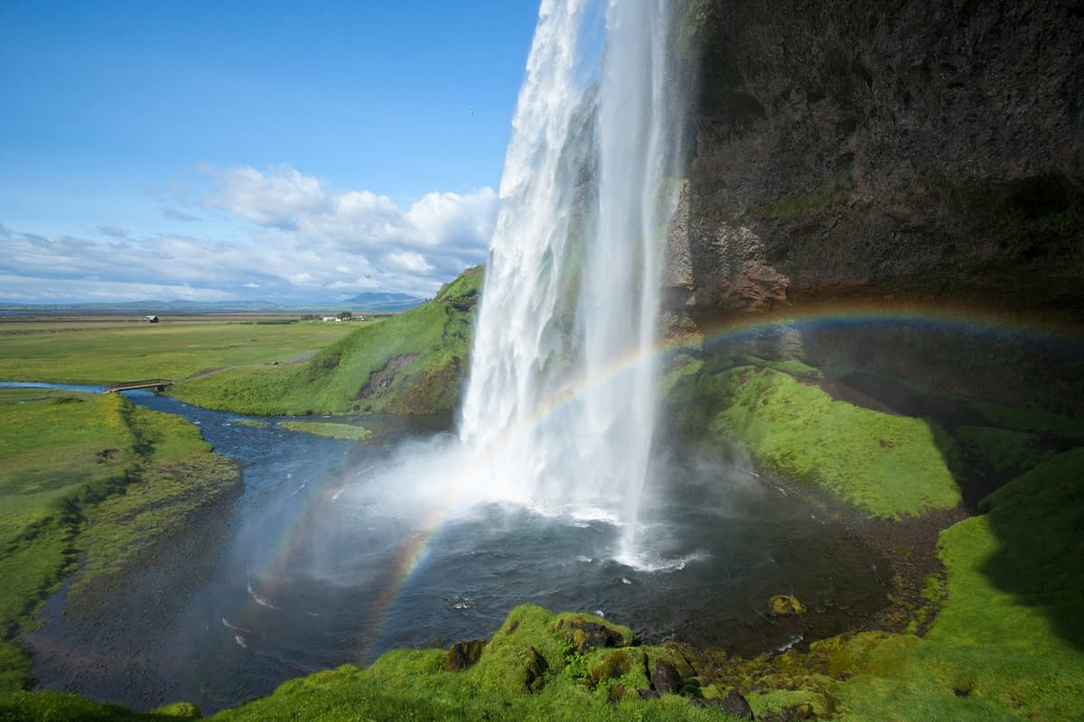 Rainbow beneath 60m-high Seljalandsfoss waterfall, Sudhurland, Iceland.