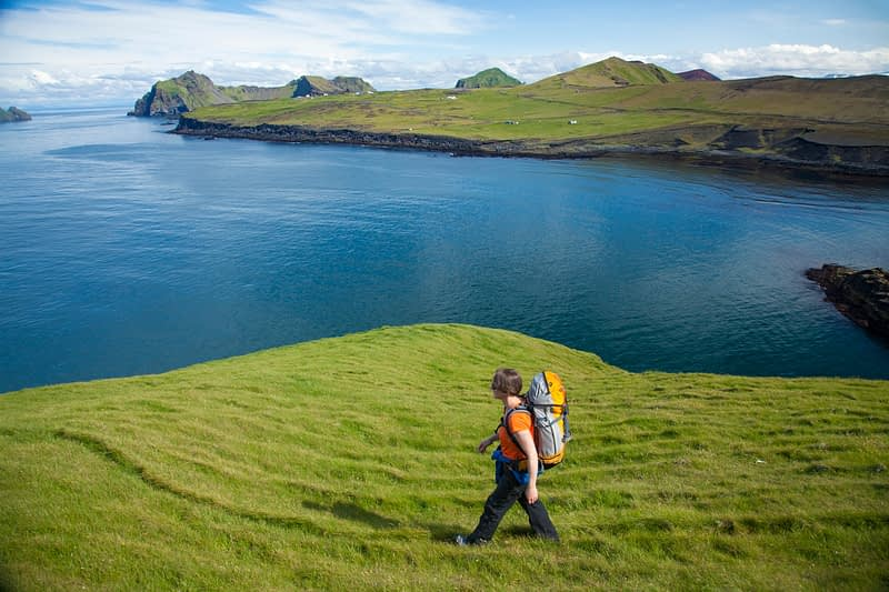 Hiker exploring the Storhofdi peninsula on Heimaey island, Westman Islands, Sudhurland, Iceland.