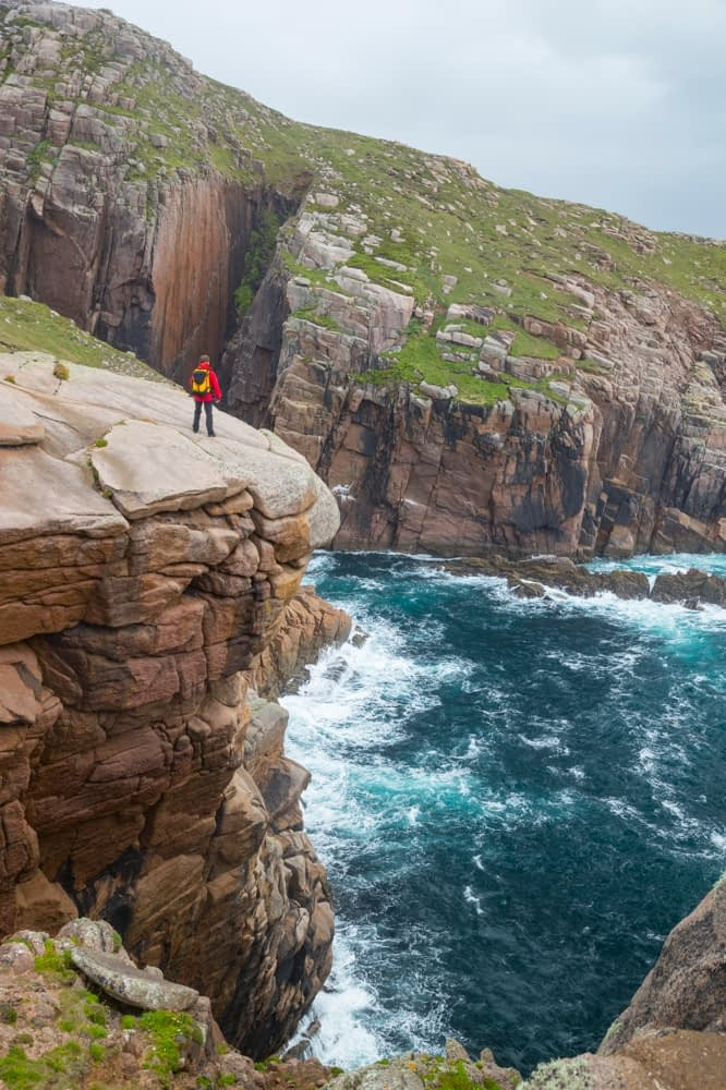 Hiker admiring the rocky coastline of Owey Island, The Rosses, County Donegal, Ireland.