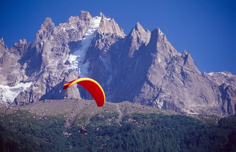 Parascending in front of the Chamonix Aiguilles, Chamonix Valley, French Alps, France.