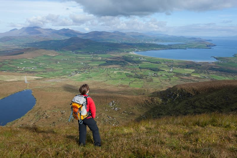 Walker looking across the Dingle Peninsula from Eagle Mountain, County Kerry, Ireland.