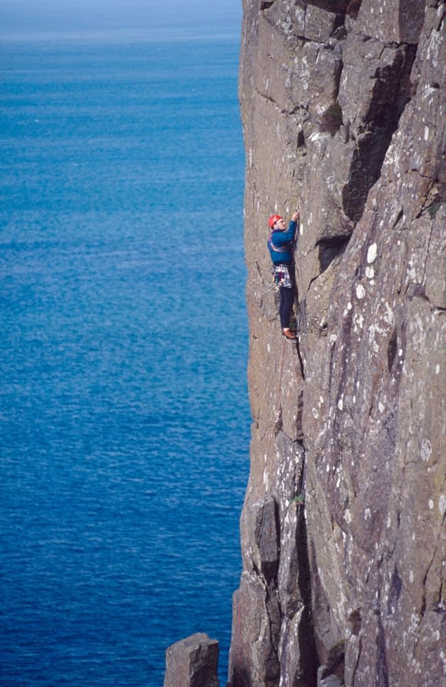 Rock climber on the cliffs of Fair Head, Co Antrim, Northern Ireland.