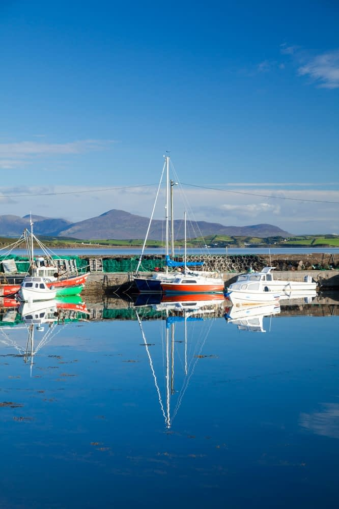 Reflection of fishing boats in Murrisk harbour, Clew Bay, County Mayo, Ireland.