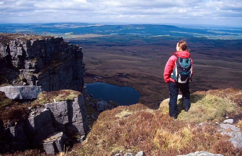 Walker on the summit of Cuilcagh Mountain, Co Fermanagh, Northern Ireland.
