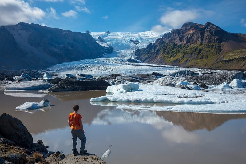 Person beside Kviarjokull glacier and moraine lake. Vatnajokull National Park, Sudhurland, south east Iceland.