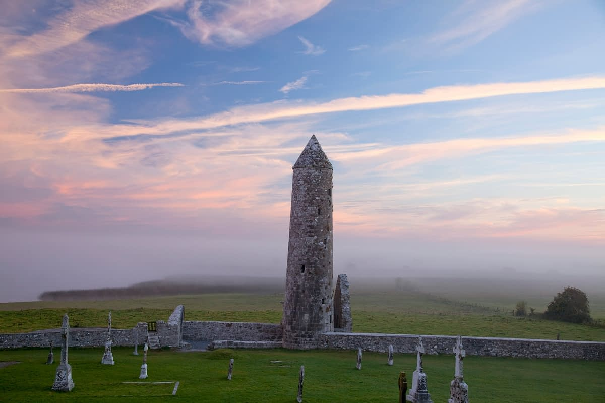 Dawn mist around Temple Finghin and round tower, Clonmacnoise, Co Offaly, Ireland.