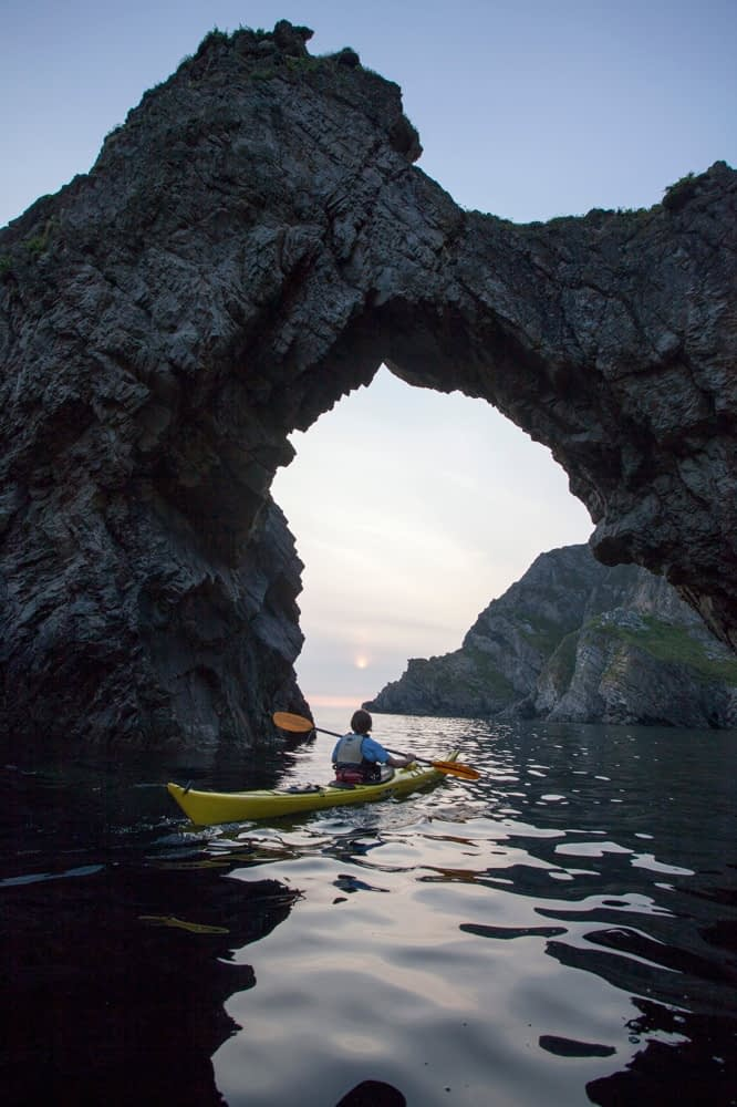 Sea kayaker beneath a rock arch in Skelpoonagh Bay, Glencolmcille, County Donegal, Ireland.
