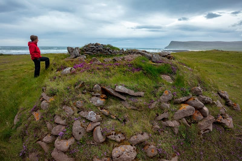 Person beside the ruins of an old fishing settlement at Brunnar, Latrabjarg Peninsula. Westfjords, Iceland.