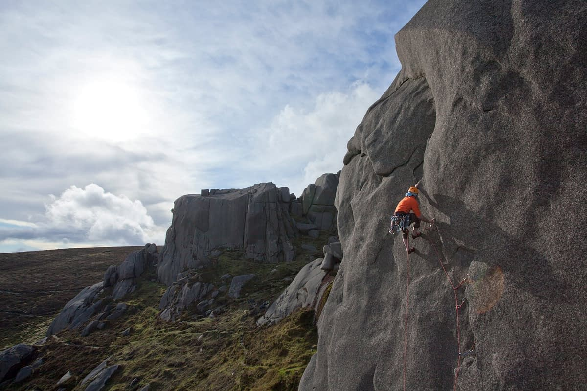 Climber on 'Electra' (E1 5b), North Tor, Slieve Binnian, Mourne Mountains, County Down, Northern Ireland.