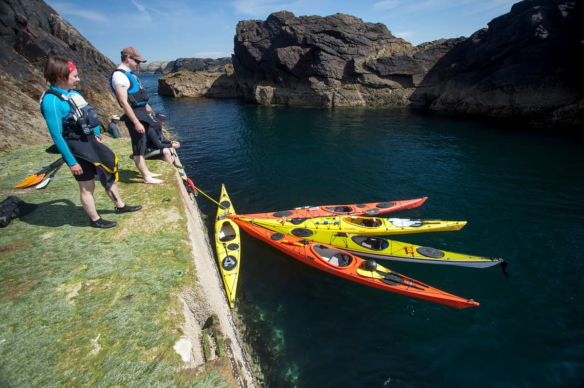 Sea kayakers landing on Eagle Island, Belmullet, County Mayo, Ireland.