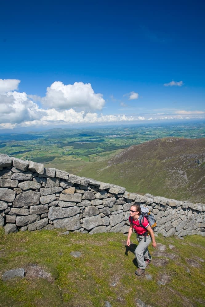 Walker beside the Mourne Wall, Slieve Bearnagh, Mourne Mountains, Co Down, Northern Ireland.
