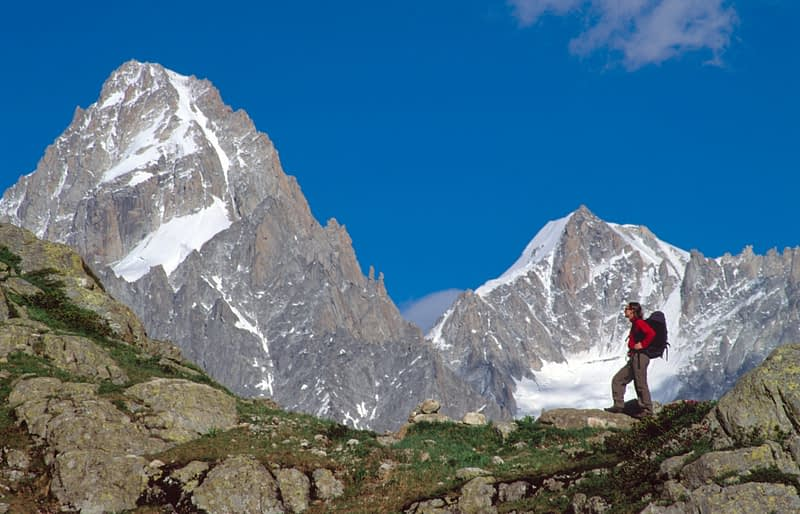 Walker beneath the peaks of the Mont Blanc massif, French Alps, France.