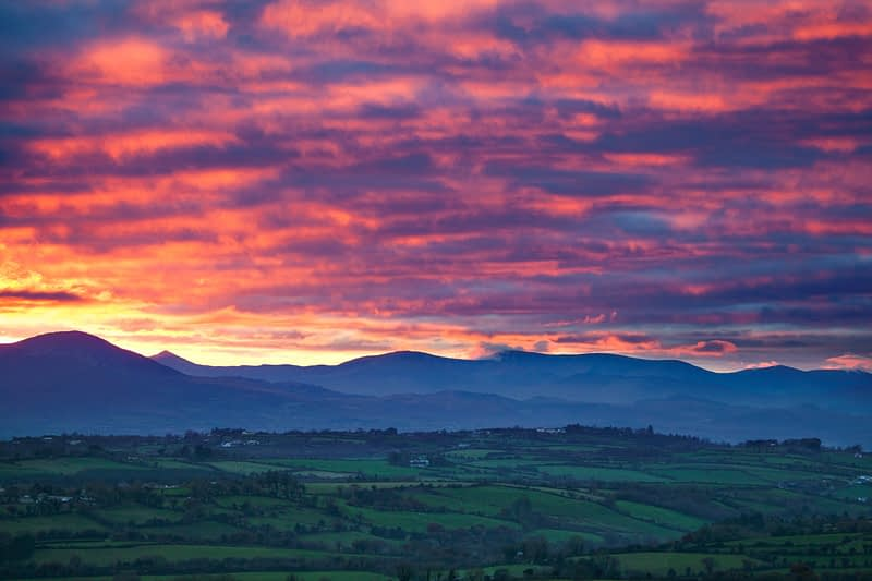 Sunset across farmland near Killarney, looking towards the hills of Iveragh, County Kerry, Ireland.