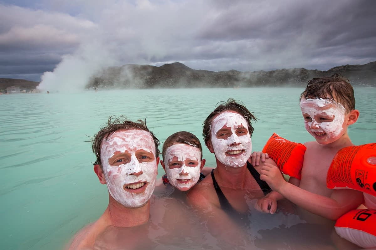 Family swimmning at the Blue Lagoon geothermal spa, Grindavik, Iceland.