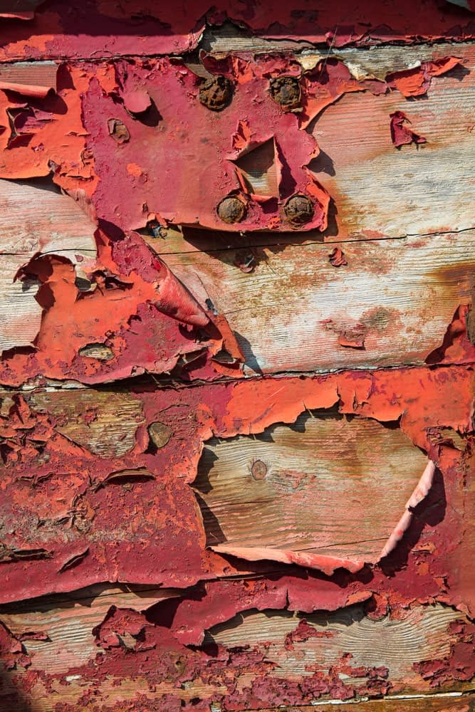 Detail of red paint peeling off an old wooden fishing boat, Ireland.