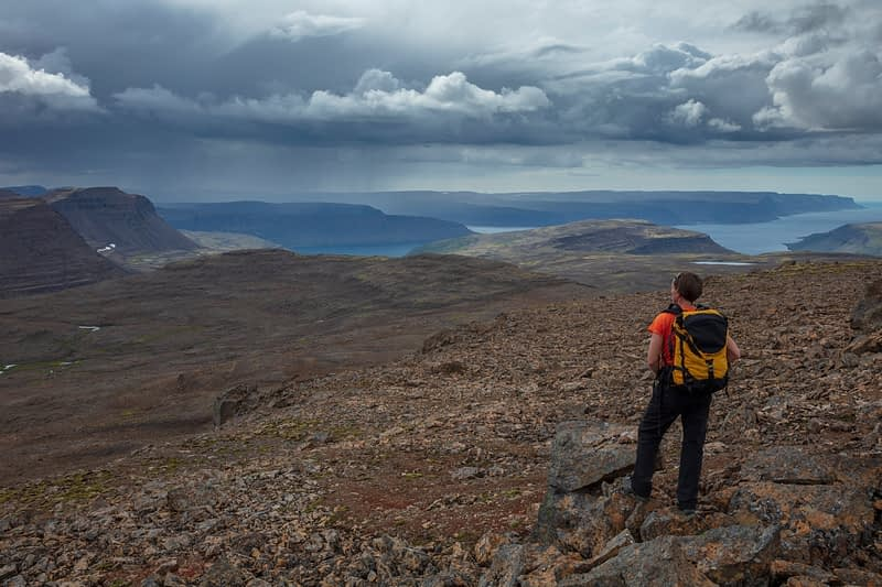 Hiker looking towards Arnarfjordur fjord from the mountain of Lomfell. Westfjords, Iceland.