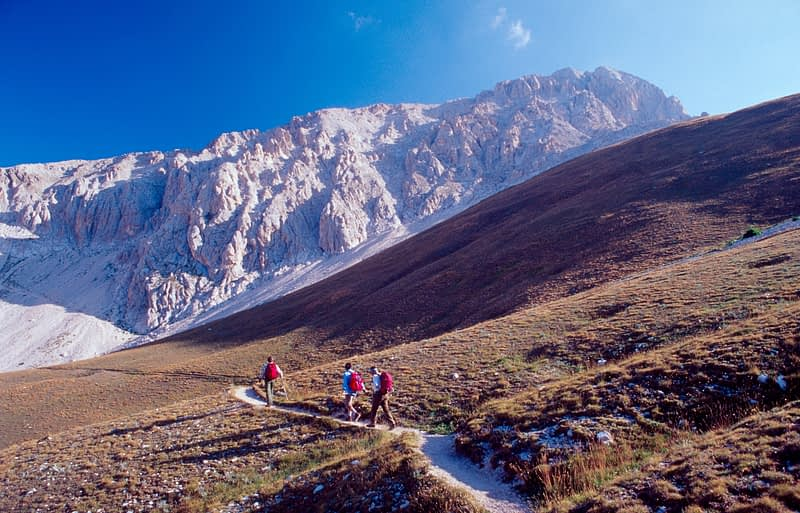 Walkers approaching Corno Grande, Gran Sasso National Park, Central Apennines, Italy.