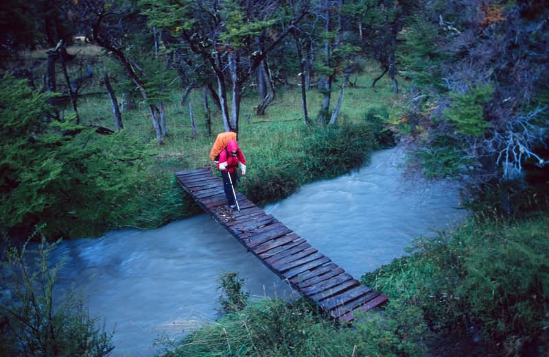 Trekker on foot bridge, Paine Circuit, Torres del Paine NP, Patagonia, Chile.