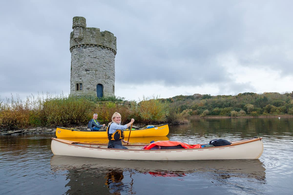 Canoeists beneath Crichton Tower, Crom Estate, Upper Lough Erne, County Fermanagh, Northern Ireland.