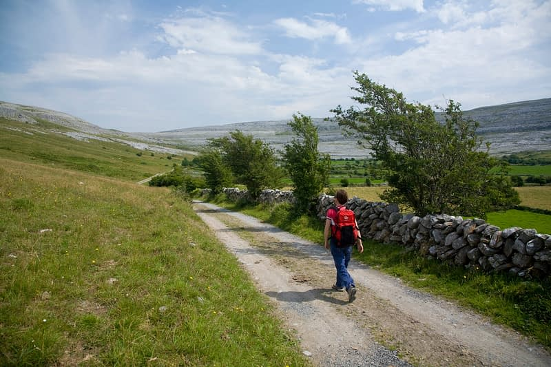 Walking along a track in the Oughtmama Valley, The Burren, Co Clare, Ireland.