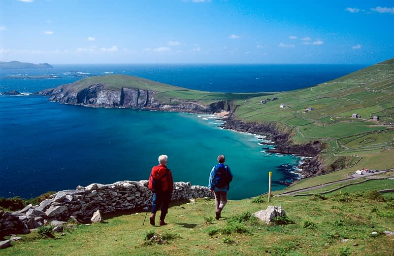 Walkers approaching Slea Head on the Dingle Way, Co Kerry, Ireland.