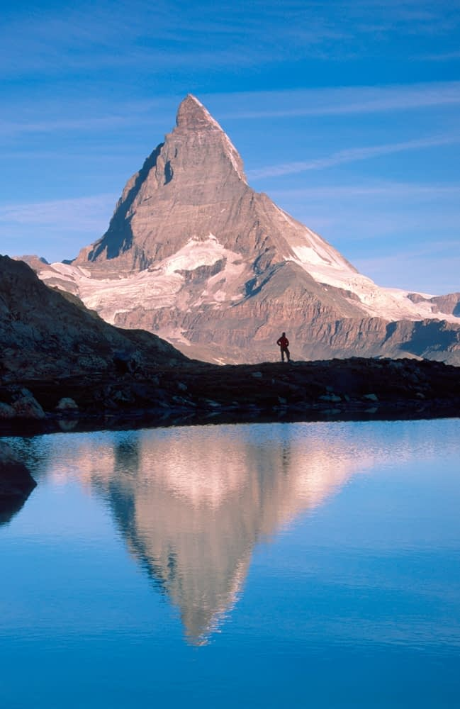 Hiker and Matterhorn reflected in the Riffelsee, Valais, Swiss Alps, Switzerland.