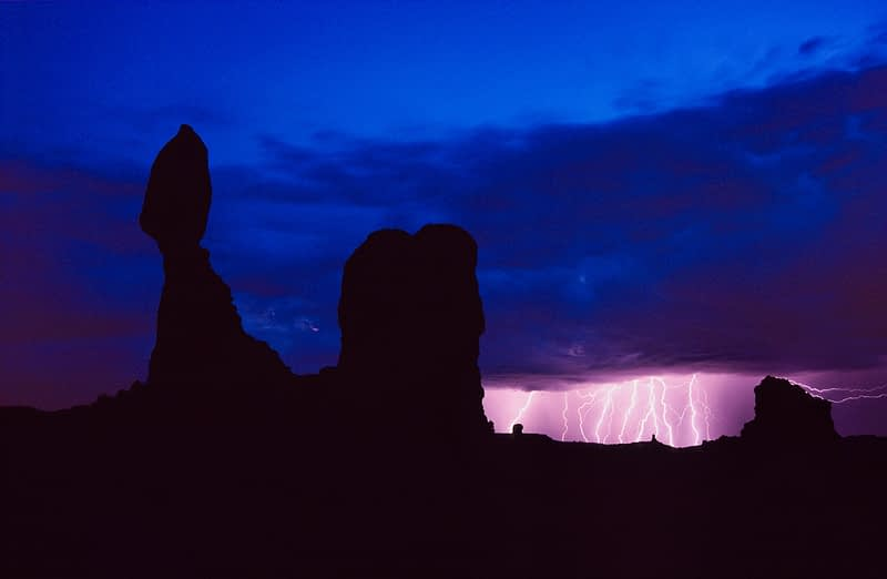 Balanced Rock silhouetted by dusk lightning, Arches National Park, Utah, USA.