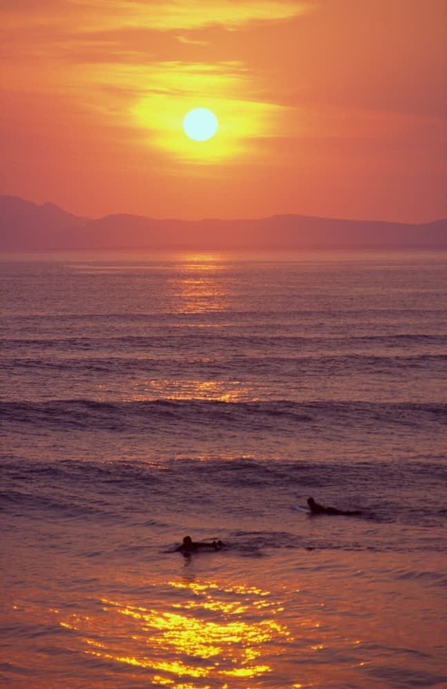 Surfers in the sea at sunset, Tullan Strand, Co Donegal, Ireland.