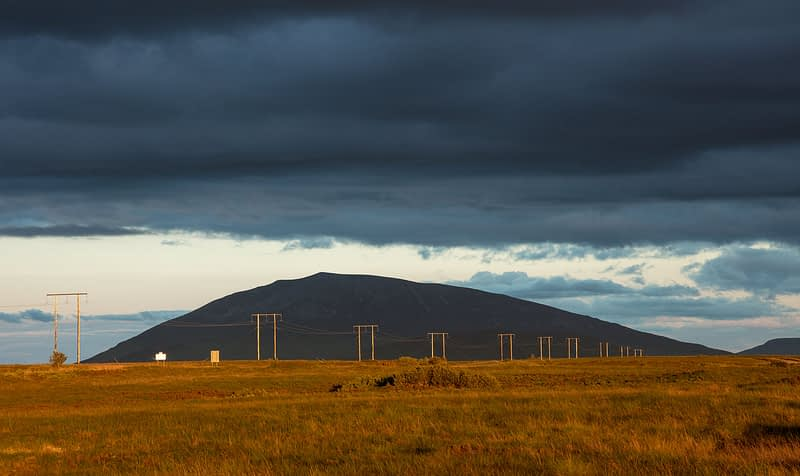 Pylons mark a country road beneath the Nephin Beg Mountains. Bellacorrick, County Mayo, Ireland.