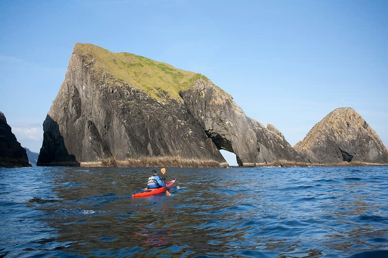 Sea kayaker exploring the Stags of Broadhaven, Portacloy, Co Mayo, Ireland.