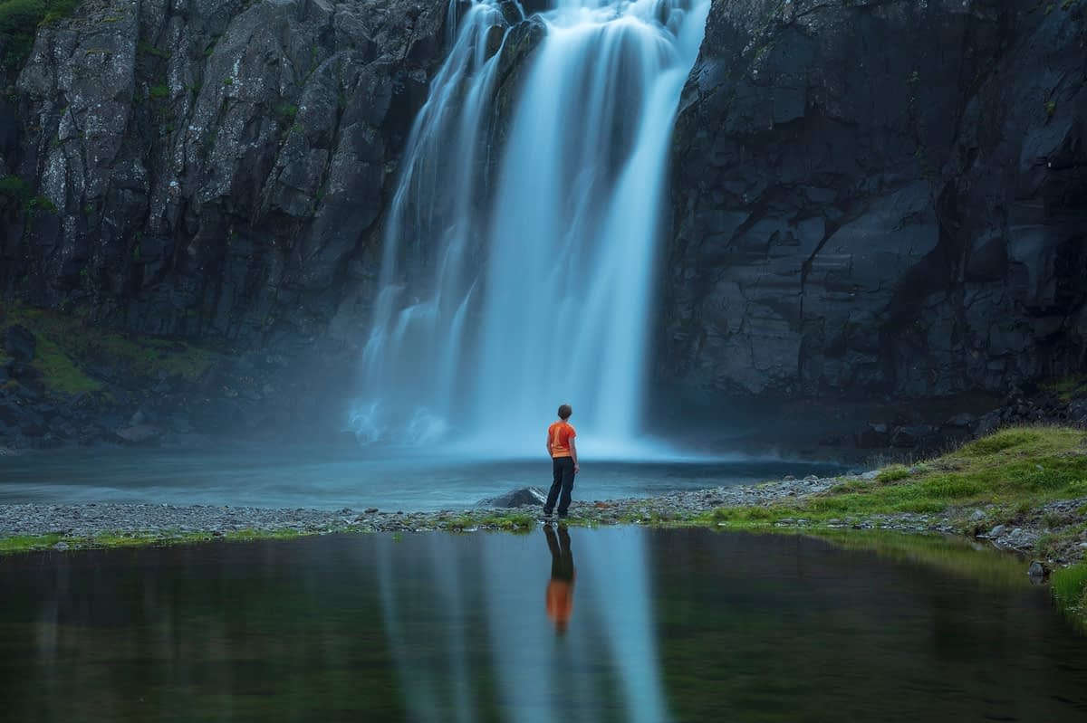 Person reflected beneath Foss waterfall, on the shore of Fossfjordur. Westfjords, Iceland.