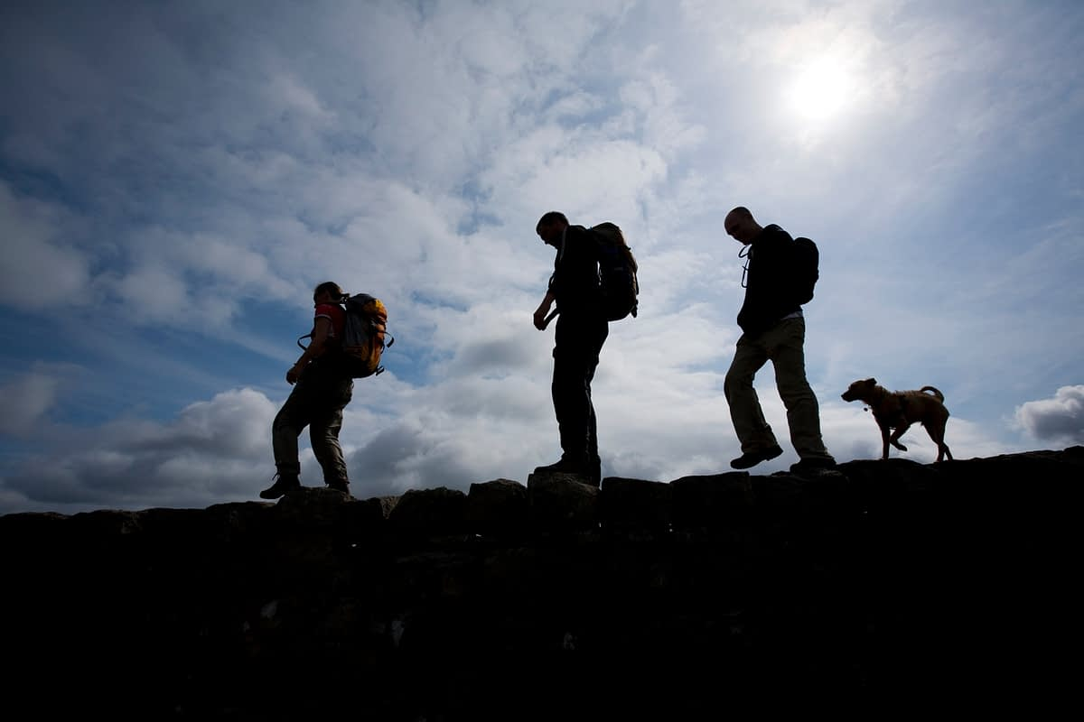 Silhouette of walkers and dog, Mourne Mountains, Co Down, Northern Ireland.