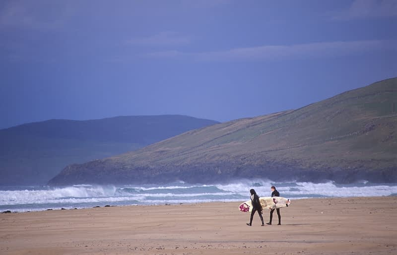 Surfers on beach, Co Donegal, Ireland.
