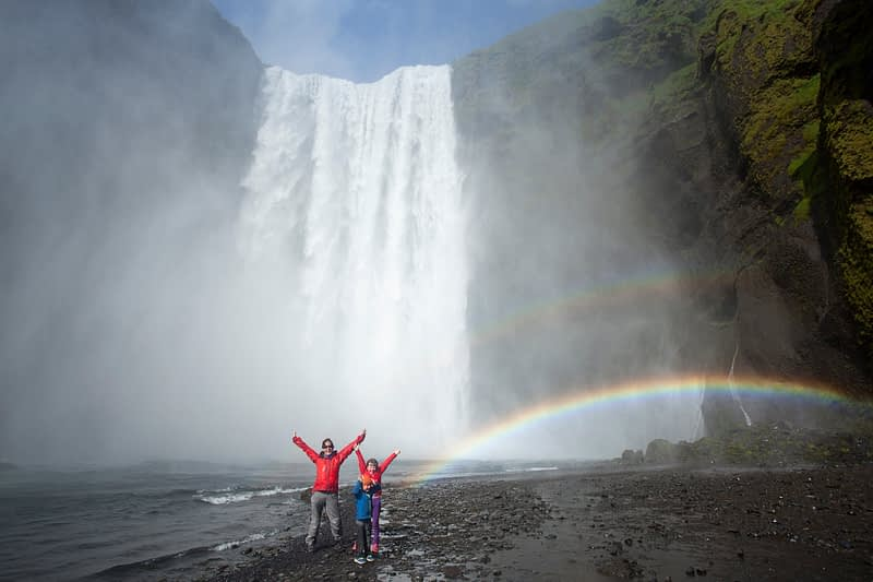 Family in the rainbow beneath 60m-high Skogafoss waterfall, Skogar, Sudhurland, Iceland.