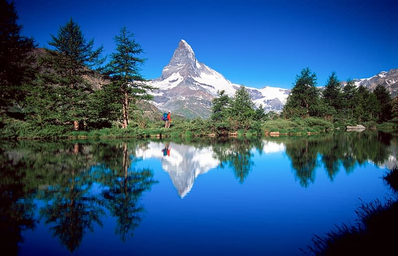 Walker and Matterhorn reflected in the Grindijsee, Valais, Swiss Alps, Switzerland.