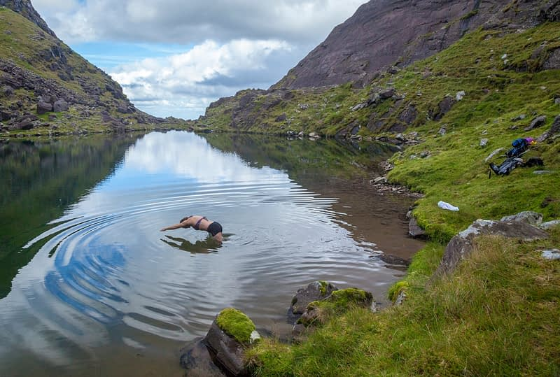 Swimming in Lough Cummeenoughter beneath Carrauntoohil. MacGillycuddy's Reeks, County Kerry, Ireland.