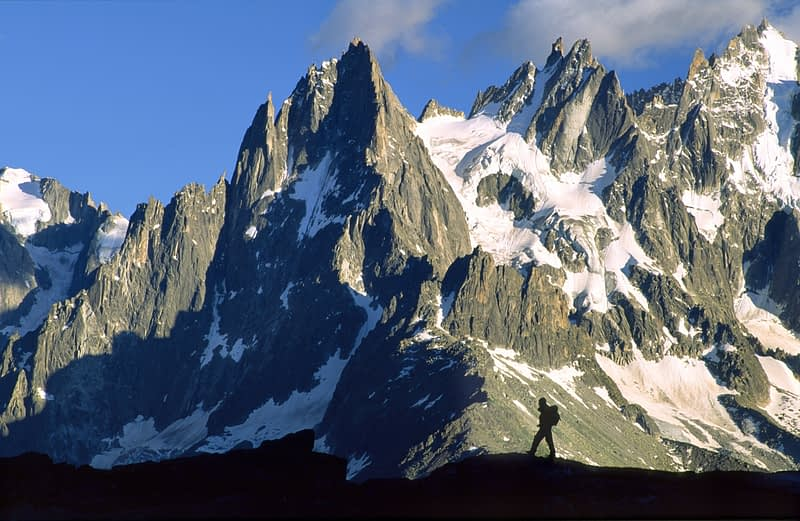 Walker silhouetted in front of the Chamonix Aiguilles, French Alps, France.