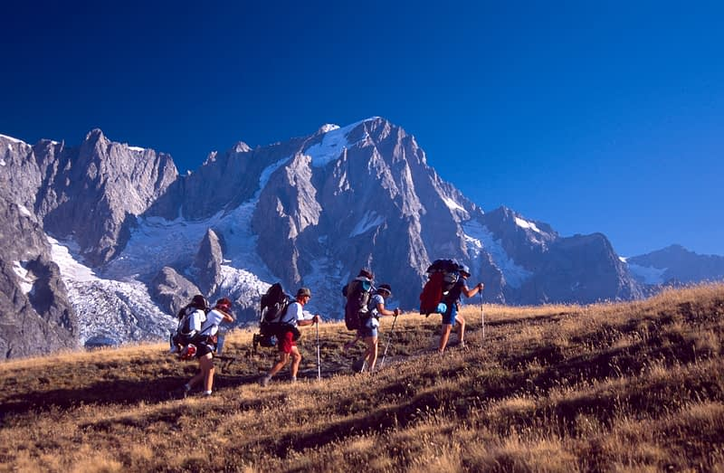 Walkers on Monte Saxe beneath the Grandes Jorasses, Tour of Mont Blanc, Italian Alps, Italy.