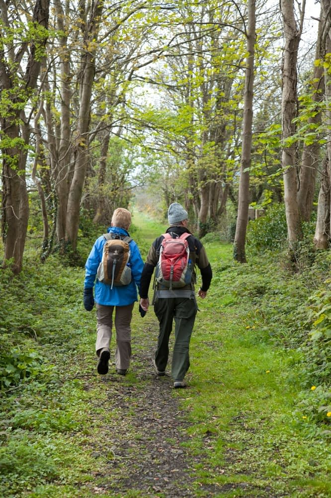 Couple walking on the Dundrum Coastal Path, County Down, Northern Ireland.