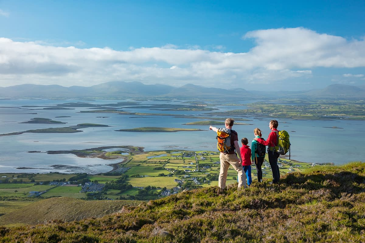 Hiking family looking over Clew Bay from the slopes of Croagh Patrick, County Mayo, Ireland.