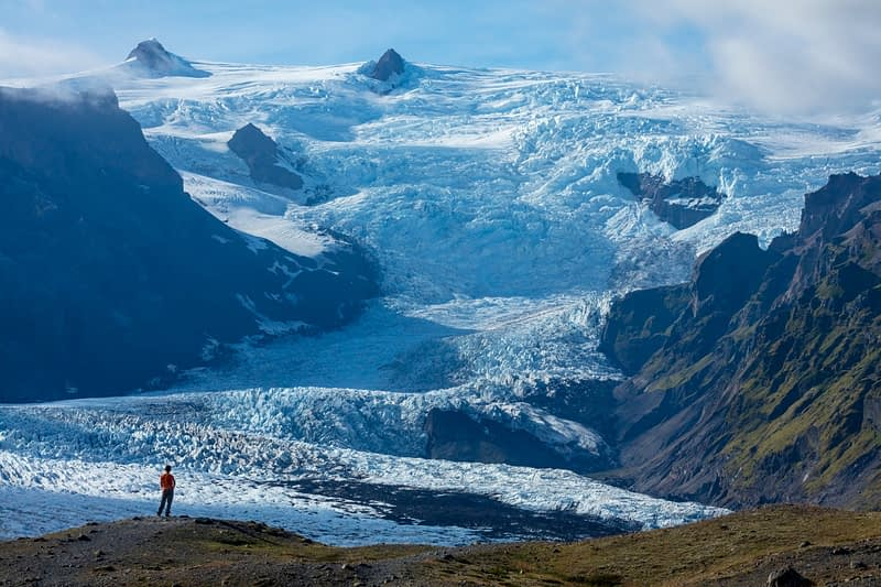 Person dwarfed by the ice fall of Kviarjokull glacier. Vatnajokull ice cap, Sudhurland, south east Iceland.