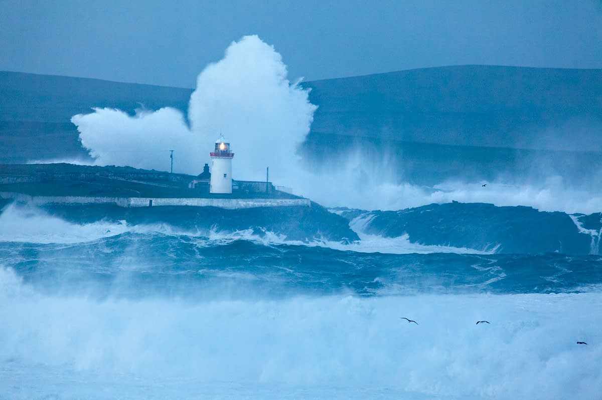Storm waves beaking over Ballyglass Lighthouse, Broadhaven, County Mayo, Ireland.