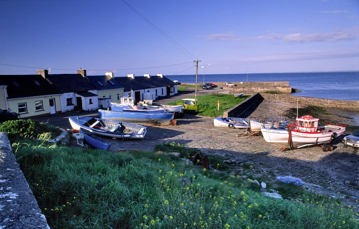Cottages and fishing boats at Kilcummin harbour, Co Mayo, Ireland.