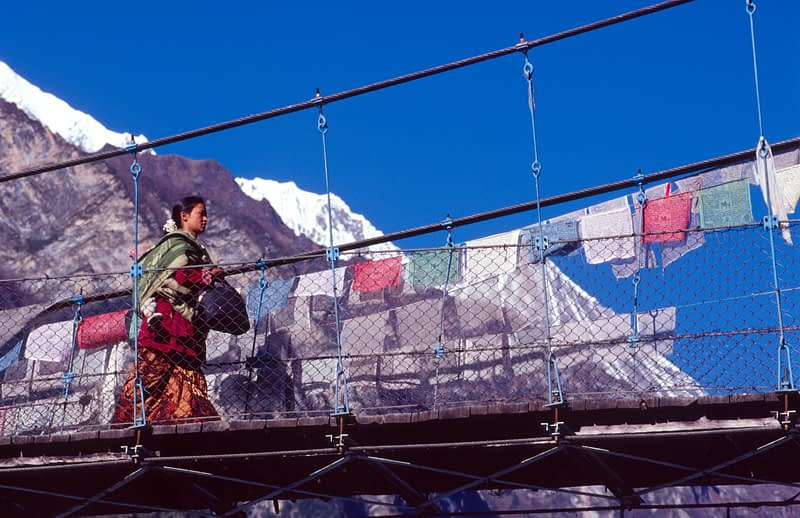 Local Nepali woman crossing a bridge on the Annapurna Circuit, Nepal.