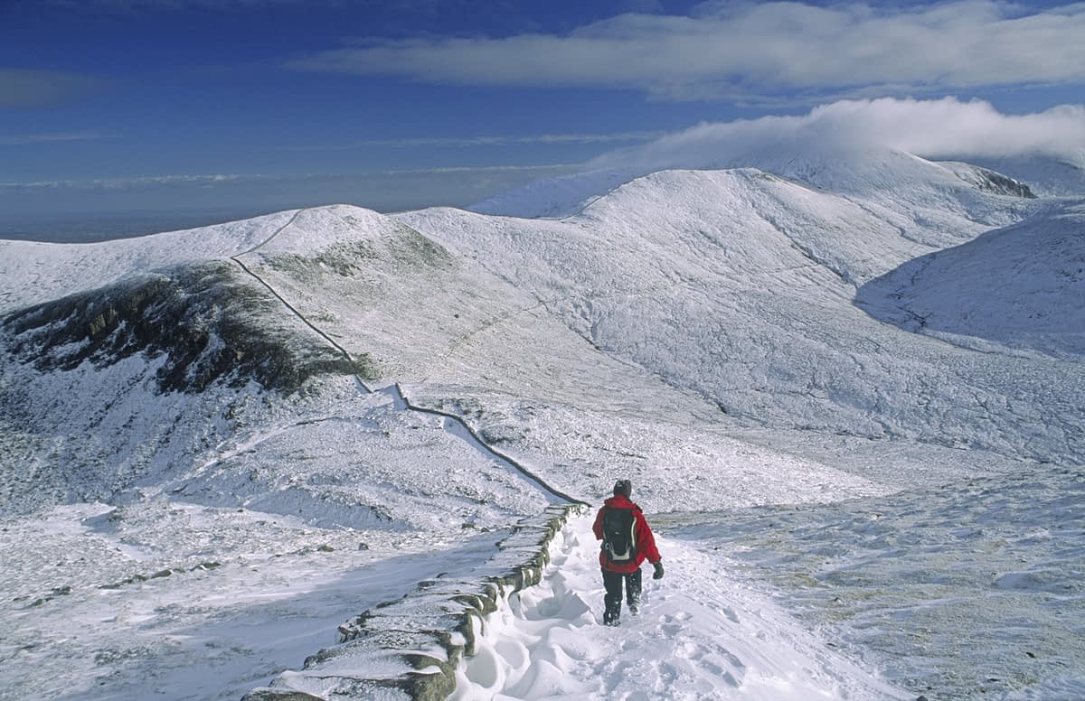 Walking along the Mourne Wall in winter, Slieve Bearnagh, Mourne Mountains, Co Down, Northern ireland.