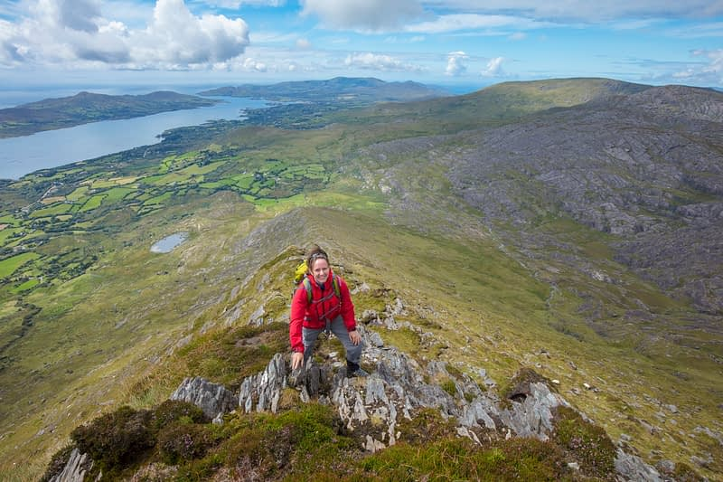 Hiker scrambling on the southwest ridge of Hungry Hill, Beara Peninsula, County Cork, Ireland.
