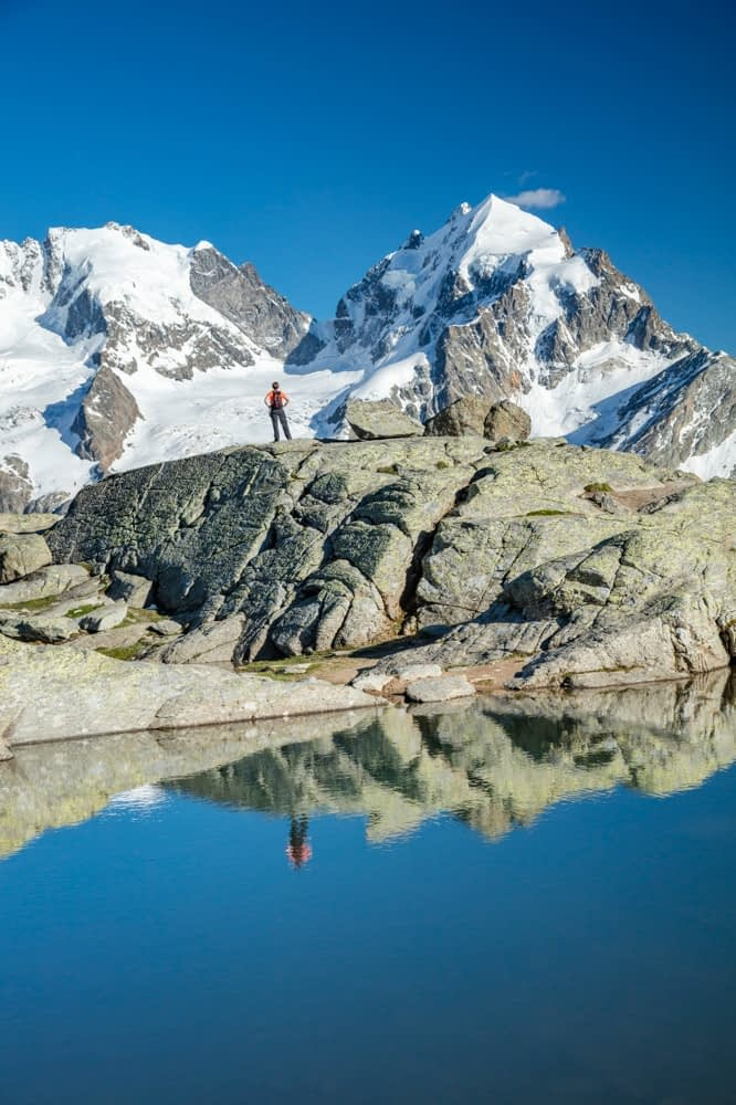 Reflection of hiker beneath Piz Bernina and Piz Rosbeg, Fuorcla Surlej, Berniner Alps, Graubunden, Switzerland.