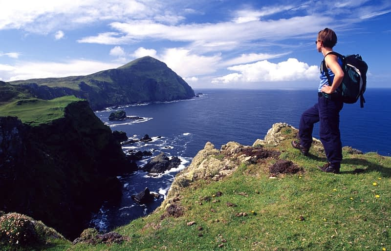 Walker admiring the seacliffs of north Clare Island, Co Mayo, Ireland.