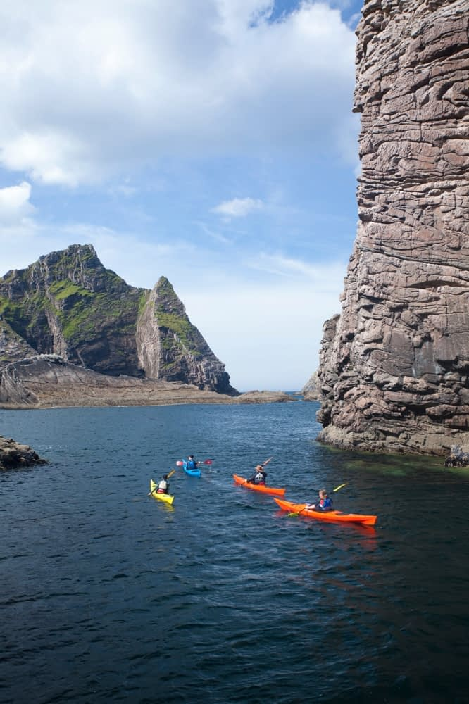Sea kayakers passing Hag Island, North Mayo seacliffs, Co Mayo, Ireland.